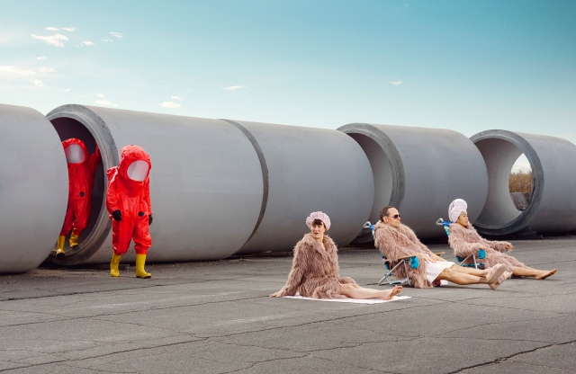 From behind a row of giant concrete pipes, two hazmat-suit-clad figures approach a group of furry-robe-wearing sunbathers.
