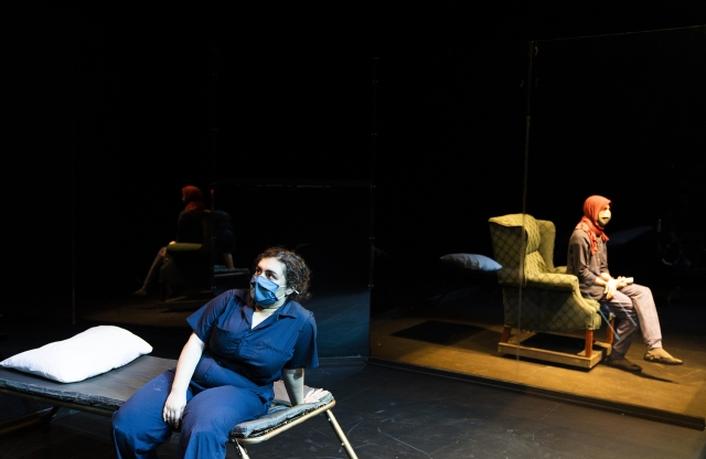 A masked woman sits on a cot looking off stage, while on the other side of a stage another masked woman with a headscarf looks in a different direction
